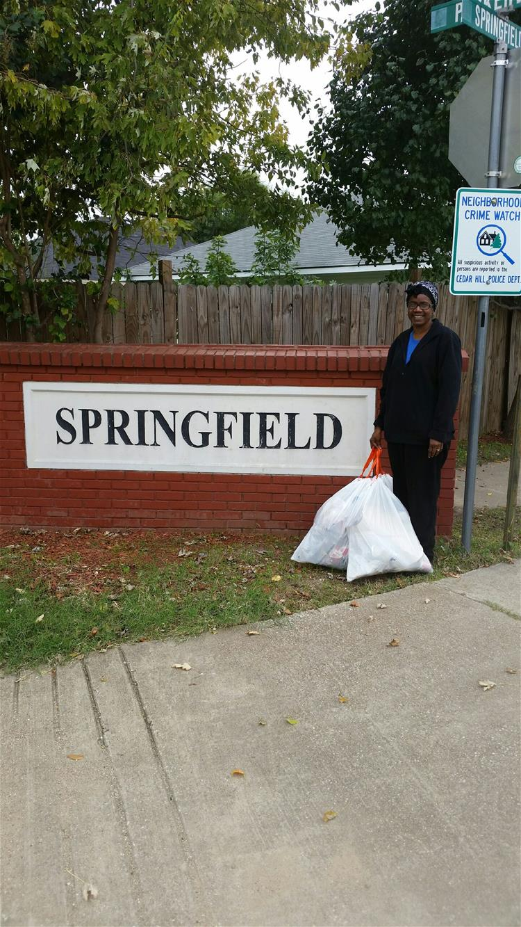 Woman with Trash Bags Standing by Springfield Sign